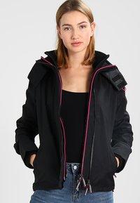 Superdry - TECH HOOD POP ZIP WINDCHEATER - Summer jacket - black/raspberry - 0