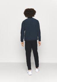 Lacoste Sport - NAMING TRACK PANT - Teplákové kalhoty - black/white - 2