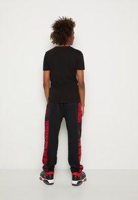 Jordan - ESSENTIALS - Tracksuit bottoms - gym red/black - 2