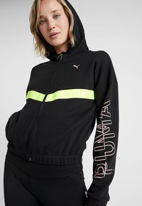 Puma - HIT FEEL IT JACKET - Zip-up hoodie - black/yellow alert