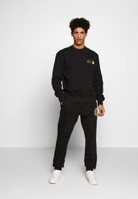 Versace Jeans Couture - PATCH JOGGERS - Verryttelyhousut - black - 1