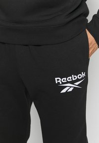 Reebok - JOGGER - Tracksuit bottoms - black - 4