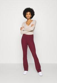 NA-KD - FLARED LOUNGE PANTS - Tracksuit bottoms - burgundy - 1