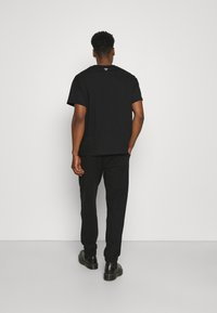 More Joy by Christopher Kane - MORE JOY EMBROIDERED CLASSSIC JOGGERS UNISEX - Tracksuit bottoms - black/white - 2