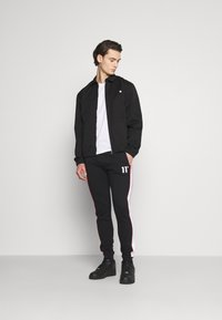 11 DEGREES - COLOUR BLOCKED PIPED JOGGERS - Tracksuit bottoms - black/white/goji berry red - 1