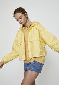 PULL&BEAR - MIT KAPUZE UND TASCHEN - Vodotěsná bunda - yellow - 3