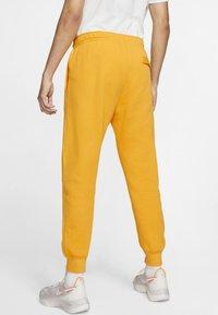 Nike Sportswear - CLUB - Tracksuit bottoms - university gold/white - 1