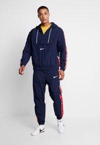 Nike Sportswear - Windbreaker - obsidian/white/university red - 1