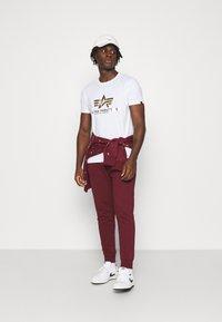 Nike Sportswear - CLUB - Tracksuit bottoms - dark beetroot/white - 1
