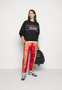 Versace Jeans Couture - PRINT BAROQUE - Tracksuit bottoms - red - 1