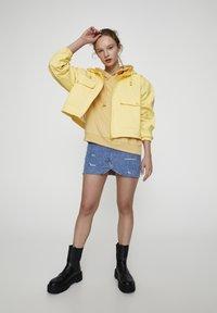 PULL&BEAR - MIT KAPUZE UND TASCHEN - Vodotěsná bunda - yellow - 1