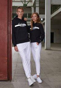Calvin Klein - REFLECTIVE CHEST STRIPE HOODIE UNISEX - Sweatshirt - black - 1