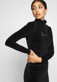 Karl Kani - SMALL SIGNATURE RHINESTONE TURTLEDRESS - Pouzdrové šaty - black - 3