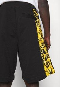 Versace Jeans Couture - PRINT LOGO BAROQUE - Tracksuit bottoms - black - 4