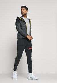 Nike Performance - PANT TRAIL - Verryttelyhousut - black/laser crimson