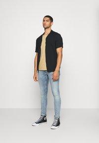 Nudie Jeans - ROGER - Camiseta básica - beige - 1