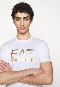 EA7 Emporio Armani - Print T-shirt - white/gold - 3