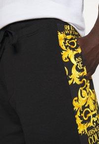 Versace Jeans Couture - PRINT LOGO BAROQUE - Tracksuit bottoms - black - 5