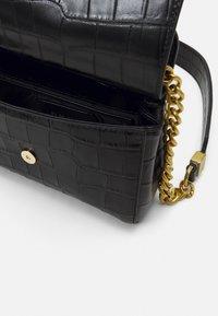 DKNY - COOPER FLAP XBODY CROCO - Handbag - black/gold-coloured - 2
