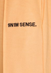 9N1M SENSE - LOGO PANTS UNISEX - Broek - pantone apricot/black - 2