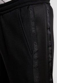Calvin Klein Jeans - INSTIT TAPE MIX MEDIA PANT - Teplákové kalhoty - black - 3