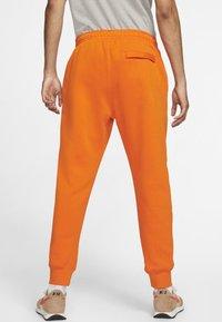 Nike Sportswear - CLUB - Tracksuit bottoms - magma orange/white - 1