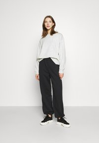NA-KD - NA-KD X ZALANDO EXCLUSIVE - LOOSE FIT PANTS - Tracksuit bottoms - black - 1