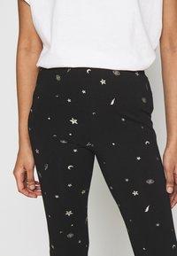 Colourful Rebel - STAR EYE PRINT BASIC FLARE PANTS - Trousers - black - 2
