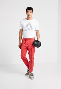Reebok - TRAINING ESSENTIALS TRACK PANTS - Tracksuit bottoms - red - 1