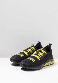 Puma - HYBRID NX CAUTION - Neutral running shoes - black/blazing yellow - 2