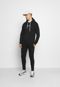 Good For Nothing - ESSENTIAL JOGGER WITH RUBBER BADGE - Tracksuit bottoms - black - 1