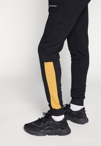 CLOSURE London - CONTRAST SCRIPT JOGGER - Tracksuit bottoms - black/mustard - 3