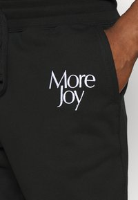 More Joy by Christopher Kane - MORE JOY EMBROIDERED CLASSSIC JOGGERS UNISEX - Tracksuit bottoms - black/white - 3