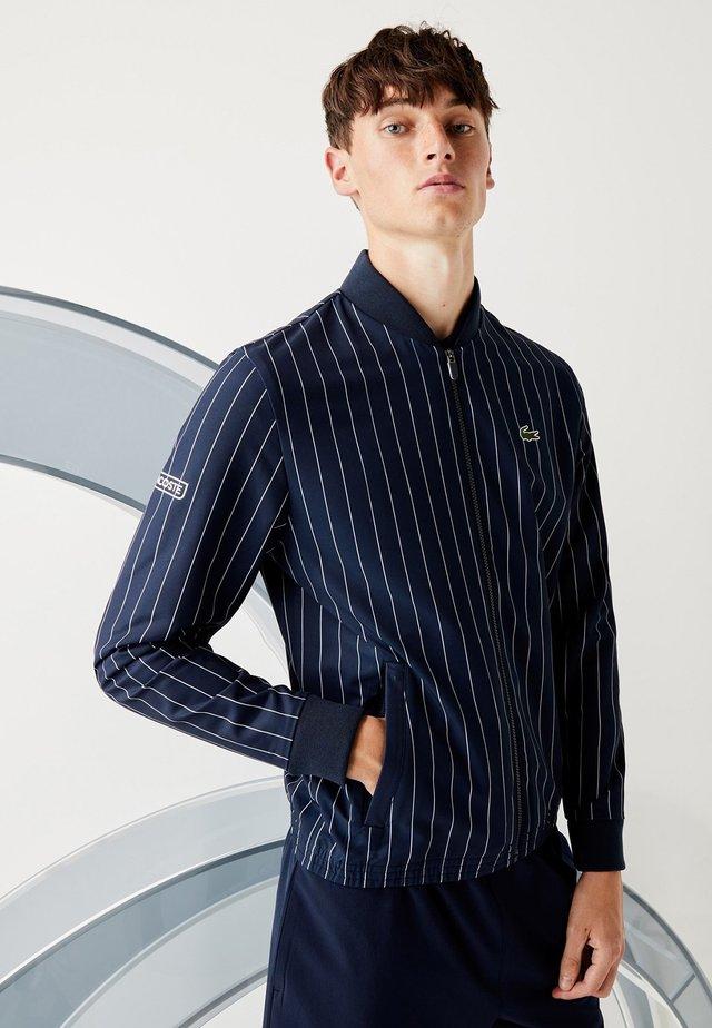 Veste de survêtement - bleu marine / blanc