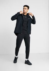 Nike Performance - Tracksuit bottoms - black/white - 1