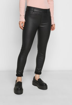 COATED EDEN - Trousers - black