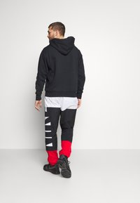 Nike Performance - STARTING PANT - Tracksuit bottoms - white/black/university red - 2