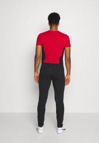Puma - AC MAILAND EVOSTRIPE PANTS - Klubbkläder - black/tango red - 2