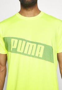 Puma - TRAIN GRAPHIC SHORT SLEEVE TEE - T-shirt print - fizzy yellow - 5