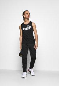 Puma - EVOSTRIPE PANTS - Pantalon de survêtement - black - 1