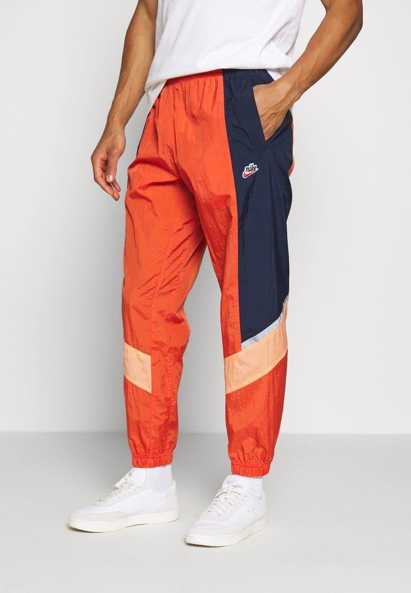 Nike Sportswear - Tracksuit bottoms - mantra orange/obsidian/orange frost