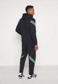 adidas Originals - TRACK PANT UNISEX - Tracksuit bottoms - black/shock lime - 2