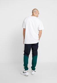 Carhartt WIP - BARNES PANT - Pantalones deportivos - dark navy / dark fir - 2