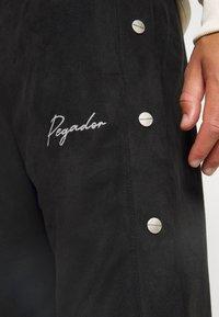 Pegador - SUEDE BUTTON PANTS UNISEX - Trousers - black - 6