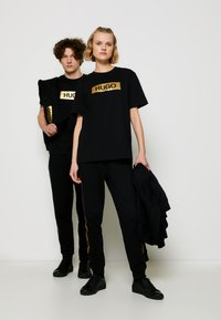 HUGO - DIRAGOLINO METALLIC UNISEX - Printtipaita - black/gold - 1