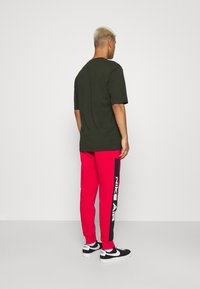Nike Sportswear - AIR - Tracksuit bottoms - university red/black/white - 2