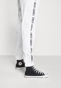 Tommy Jeans - JOGGER TAPE RELAXED - Tracksuit bottoms - white - 3