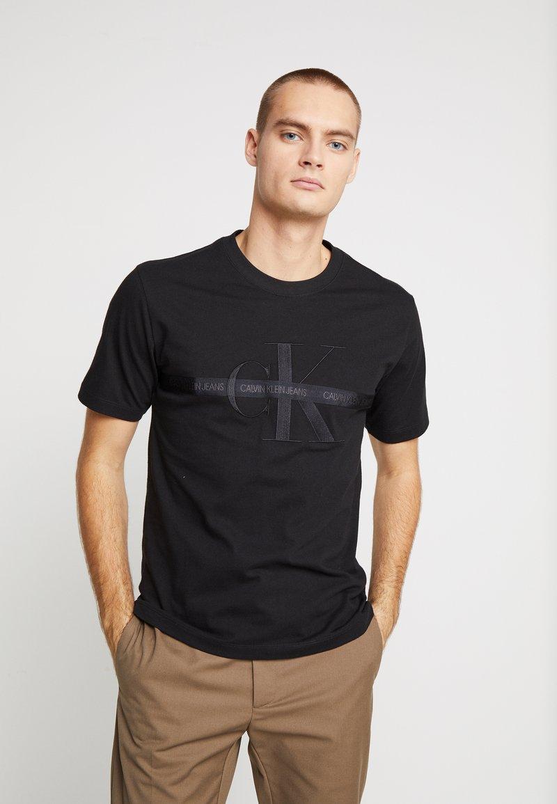 Calvin Klein Jeans - TAPING THROUGH MONOGRAM REG TEE - T-shirt med print - black