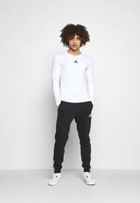 adidas Performance - DK ESSENTIALS - Tracksuit bottoms - black/white - 1
