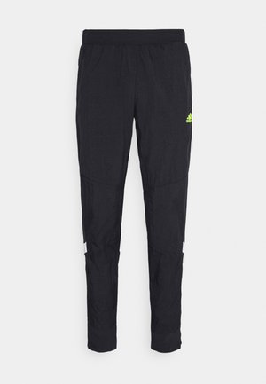 ULTRA PANT - Tracksuit bottoms - black/yellow
